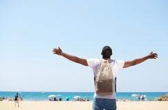Mens die zich met uitgespreid wapens open bij strand bevinden Royalty-vrije Stock Fotografie