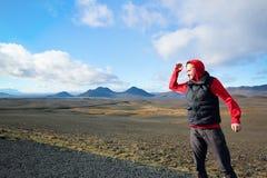 Mens die zich op de achtergrond van de bergen in IJsland bevinden stock fotografie