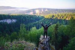 Mens die zich op de bovenkant van de berg met opgeheven handen bevinden Royalty-vrije Stock Afbeelding