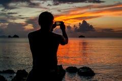 Mens die zich op de kust van een tropisch eiland bevinden en de zonsondergang fotograferen uw telefoon Stock Fotografie