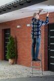 Mens die zich op de ladder en het aanhalen het ventilatietraliewerk bevinden Royalty-vrije Stock Afbeelding