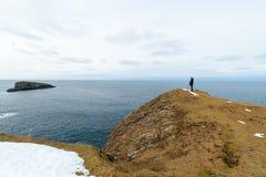Mens die zich op de rand van klippen, Shetland-eilanden bevinden Royalty-vrije Stock Afbeelding