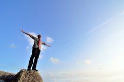 Mens die zich op de rots met zijn wapens brede open bevinden royalty-vrije stock foto