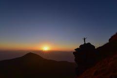 Mens die zich op de rots tijdens zonsondergang bij de berg bevinden Royalty-vrije Stock Foto's