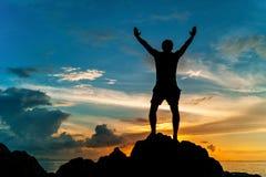 Mens die zich op de rots van een tropisch eiland met zijn handen bevinden omhoog en op de zonsondergang letten Royalty-vrije Stock Afbeelding