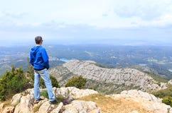 Mens die zich op een berg bevinden en een vallei bekijken Royalty-vrije Stock Afbeelding