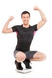 Mens die zich op een gewichtsschaal en een gesturing vreugde bevinden Royalty-vrije Stock Foto's