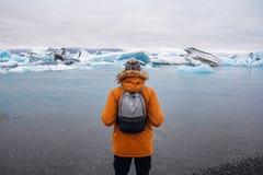 Mens die zich op een ijs in een gletsjerlagune jokulsarlon IJsland tijdens een mooie zonnige dag bevinden stock afbeelding