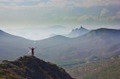 Mens die zich op een klip in bergen met omhoog handen bevinden Stock Afbeeldingen
