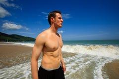 Mens die zich op exotisch strand bevindt stock foto