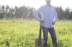 Mens die zich op het de zomergebied bevinden en akoestische gitaar houden Co Stock Afbeeldingen