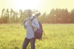 Mens die zich op het de zomergebied bevinden met akoestische gitaar en rugzak Het concept van de de zomerreis Stock Foto