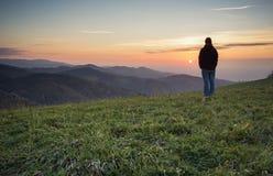 Mens die zich op heuvel in zwart bos bij zonsondergang bevinden Stock Foto