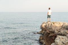 Mens die zich op mediterrane klippenbovenkant bij de zonsondergang bevinden stock afbeeldingen