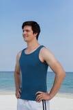 Mens die zich op strand met hand op heupen bevinden royalty-vrije stock foto