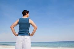 Mens die zich op strand met hand op heupen bevinden royalty-vrije stock fotografie