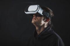 Mens die zich in virtuele werkelijkheidshelm vóór donkere achtergrond bevinden Stock Foto's
