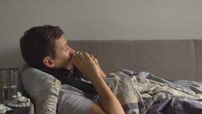 Mens die ziek in bed naast zijn medicijnen in zijn huis liggen en zijn neus in een zakdoek blazen stock footage