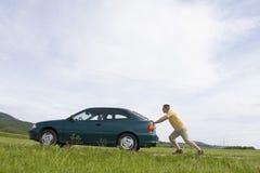 Mens die zijn auto duwt royalty-vrije stock afbeeldingen