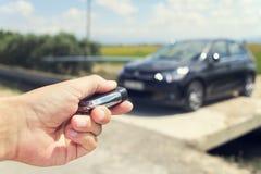 Mens die zijn auto met de controle verre sleutel openen, in openlucht, filte stock foto
