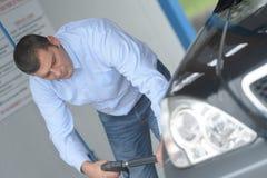 Mens die zijn auto schoonmaken stock foto