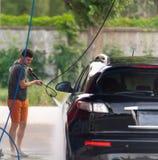Mens die zijn auto wast stock foto