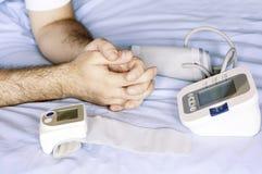 Mens die zijn bloeddruk willen meten Stock Foto