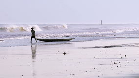 Mens die zijn boot langs het strand draging stock video