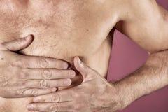 Mens die zijn borst met beide handen houden, die hartaanval of pijnlijke klemmen, die op borst met pijnlijke uitdrukking op blauw stock afbeeldingen
