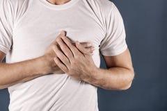 Mens die zijn borst met beide handen houden, die hartaanval of pijnlijke klemmen, die op borst met pijnlijke uitdrukking op blauw royalty-vrije stock afbeelding