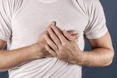 Mens die zijn borst met beide handen houden, die hartaanval of pijnlijke klemmen, die op borst met pijnlijke uitdrukking op blauw stock afbeelding