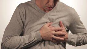 Mens die zijn borst met beide handen houden, die hartaanval of pijnlijke klemmen, die op borst met pijnlijke uitdrukking op witte stock videobeelden