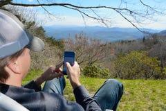 Mens die zijn cellphone gebruiken Stock Afbeelding