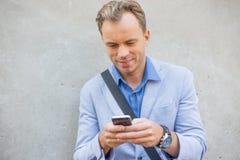 Mens die zijn cellphone gebruiken Stock Foto's