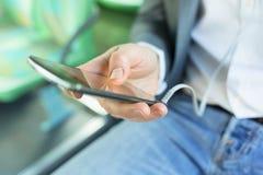 Mens die zijn celtelefoon met behulp van Luister muziek Bij bus het texting messag royalty-vrije stock fotografie