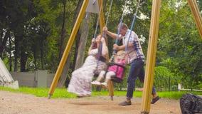 Mens die zijn dochter en zijn vrouw op een schommeling slingeren stock videobeelden