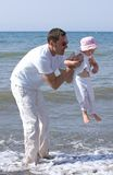 Mens die zijn dochter opheft en in het overzees speelt Stock Foto