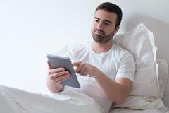 Mens die zijn elektronische tablet gebruiken die in het bed liggen Stock Foto