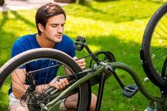 Mens die zijn fiets herstellen Stock Foto