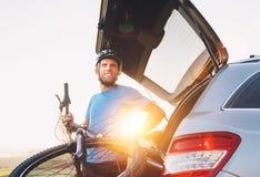 Mens die zijn fiets van de boomstam van een auto nemen stock afbeelding