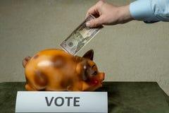 Mens die zijn geld zetten in piggi-bank op lijst royalty-vrije stock foto's