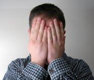 Mens die zijn gezicht behandelt stock foto