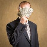 Mens die zijn gezicht met een handvol geld verbergen royalty-vrije stock fotografie