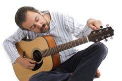 Mens die zijn gitaar stemt Stock Afbeelding