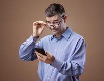 Mens die zijn glazen aanpast stock fotografie