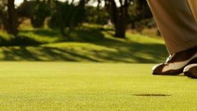 Mens die zijn golfbal en het toejuichen zetten stock video