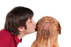 Mens die zijn grappige hond kust die op wit wordt geïsoleerde Royalty-vrije Stock Afbeeldingen
