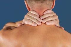 Mens die zijn die hals in pijn houden, op blauwe achtergrond wordt geïsoleerd Lagere halspijn Shirtless mens wat betreft zijn hal stock afbeeldingen