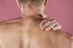 Mens die zijn die hals in pijn houden, op roze achtergrond wordt geïsoleerd Lagere halspijn Shirtless mens wat betreft zijn hals  stock fotografie