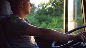 Mens die zijn hand op het stuurwiel houden en een vrachtwagen drijven bij landweg op zonnige de zomerdag Progile van Kaukasisch stock videobeelden